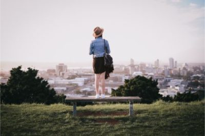 girl on a bench overlooking a city in New Zealand