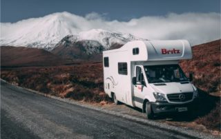 A Britz Campervan parked in front of snow capped mountains