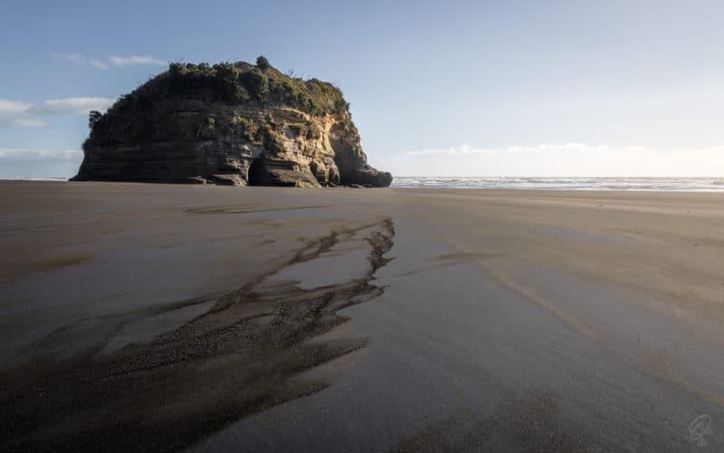 An elephant shaped rock on a black sand beach