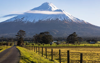mt taranaki with a wispy cloud and lush fields