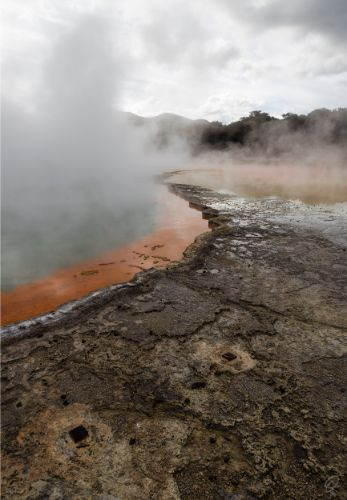 An image of champagne pools at Wai-o-Tapu showing the geothermal activity and sulphuric colours of the rock