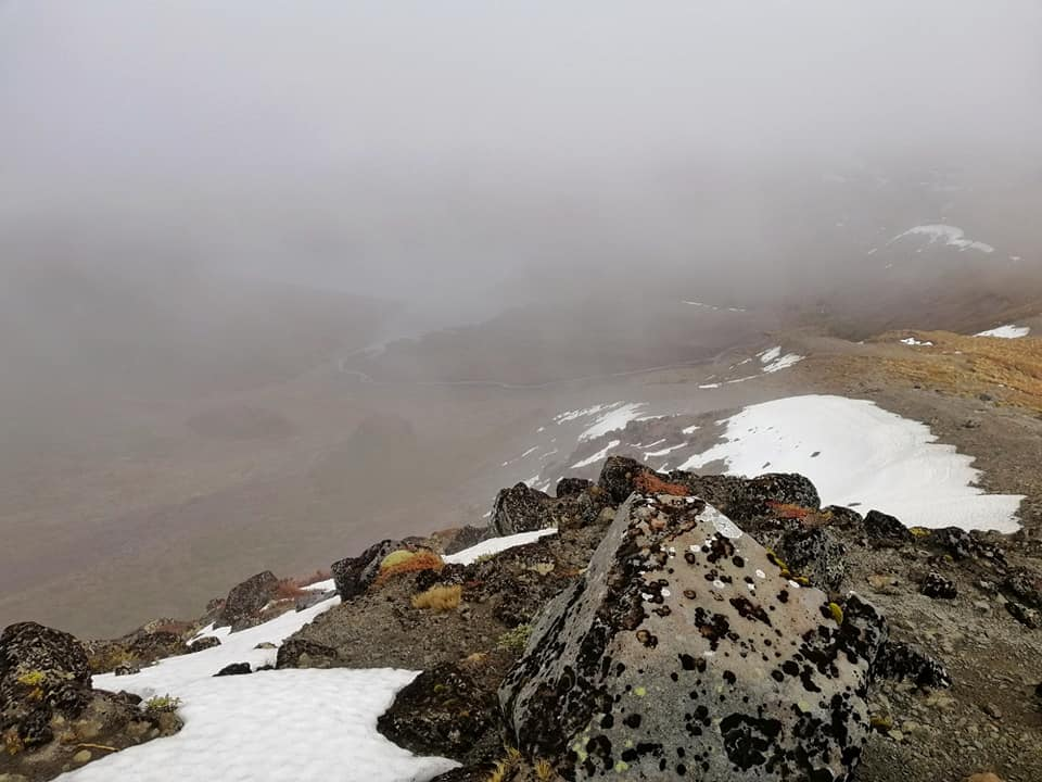 Snow on the mountain with fog rolling in across Tama Lake