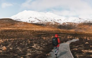 Leah walking through alpine fields with snow on mount doom