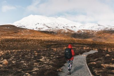 Leah walking through alpine fields with snow on mount doom